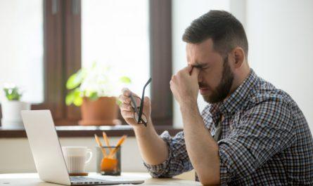 zmęczony mężczyzna przed laptopem