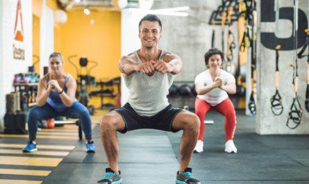 trzy osoby robią przysiady na siłowni