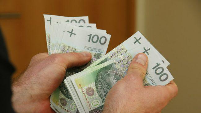 mężczyzna trzyma kilkaset złotych