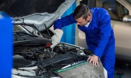mezczyzna naprawia silnik samochodu