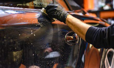 mezczyzna myje samochod gabka